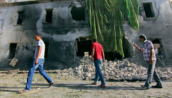 People gather at the site of a car bombing in Benghazi, Libya, on Sept. 11, 2013.