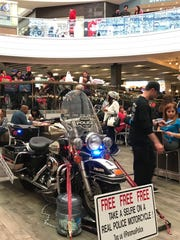 A kiosk selling merchandise to support the Policy Unity Tour let shoppers take their picture on a Paramus Police motorcycle.