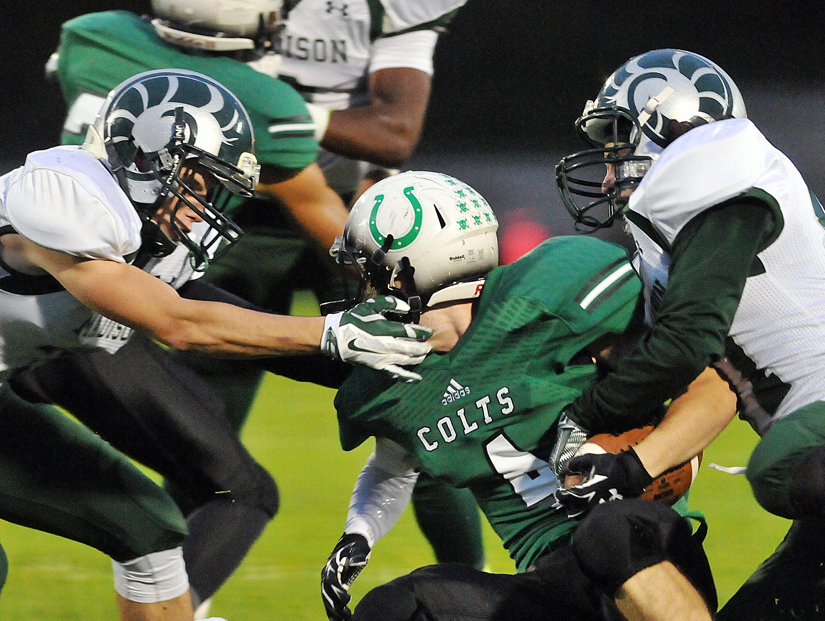 Clear Fork's Mason Buck gets wrapped up by Madison defenders during their game Friday night at Clear Fork.