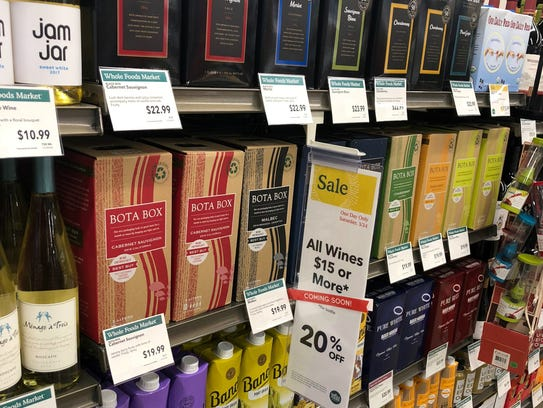 Whole Foods Market has four shelves of boxed wine varieties.