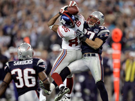 FILE - In this Feb. 3, 2008, file photo, New York Giants receiver David Tyree (85) catches a pass while in the clutches of New England Patriots safety Rodney Harrison (37) as James Sanders (36) watches during the fourth quarter of the Super Bowl XLII football game in Glendale, Ariz. A win Sunday night, Feb 1, against the Seattle Seahawks would even the Patriots record in Super Bowls at University of Phoenix Stadium at 1-1. New England is seeking a championship, not closure for its 17-14 loss to the New York Giants in 2008. (AP Photo/Gene Puskar, File) ORG XMIT: NY181