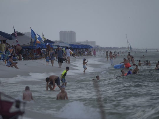 Rain falls and people play in the surf zone at Pensacola