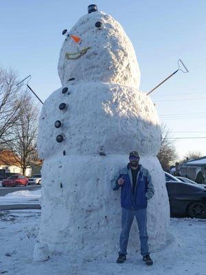 Alan Burke stands on Wednesday, Jan. 29, 2014, in front of the 18-foot-tall snowman he and his brother, Eric, created using the snow from Alan's yard.