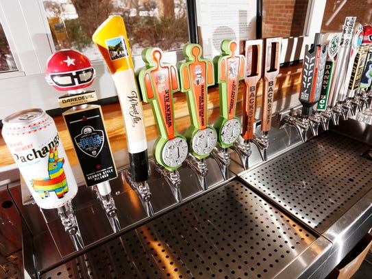 Tap handles from a variety of craft beers Monday, February