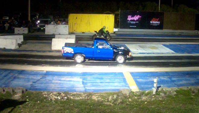 A cafe bike goes up against a Toyota truck on April 13 at the Guam International Raceway. It was test and tune night, and the races originally scheduled for the following day were pushed back a week.