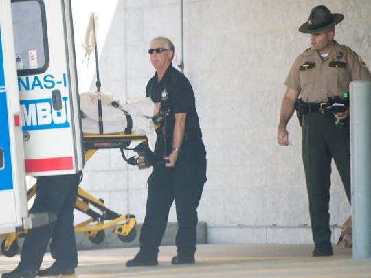 A Vermont State Police trooper escorts a Newport Ambulance Service crew unloading a conscious man at Fletcher Allen Health Care in Burlington following a shooting at the Cumberland Farms in downtown Morrisville on Wednesday afternoon. The shooting prompted schools in the area to be secured and led to a large police response.