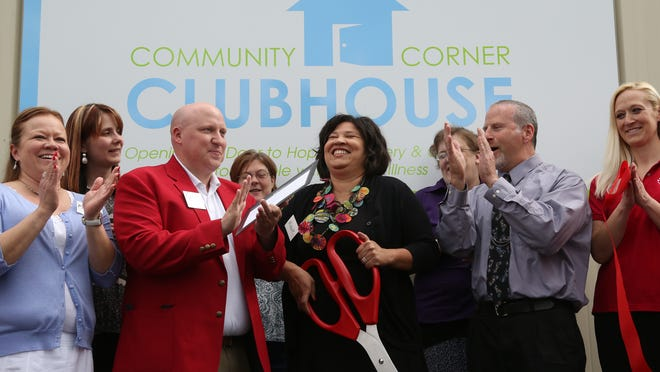 Director of of the Community Corner Clubhouse in Wausau, Michelle Hazuka, center, reacts after cutting the ribbon for the facility, Thursday, May 21, 2015. To her immediate right is Matthew Woller an ambassador from the Wausau Region Chamber of Commerce and to her immediate left is Mike Frankel a case worker at Community Corner.