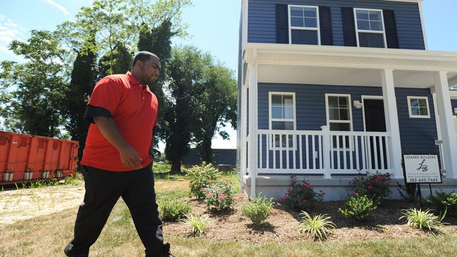 Stephen Walker walks outside his home on South Kirkwood Street in downtown Dover on Thursday. Habitat for Humanity built the home, one of five being constructed on the block.