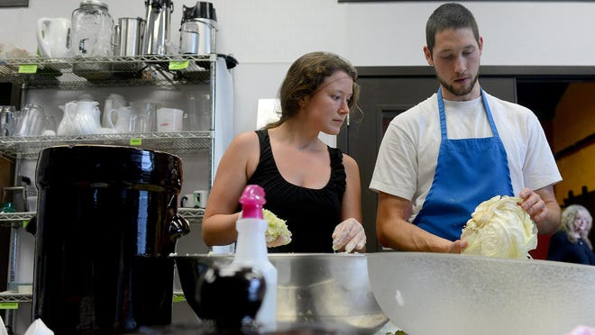 Brad Fierro, right, and Elise Thorp, co-founders of Cultured, look over cabbage for making sauerkraut in the Allen Street Market kitchen. Cultured is an 8-month-old fermenting business.