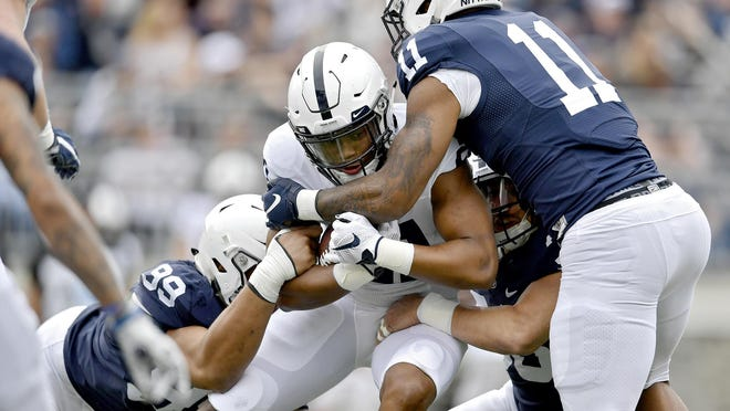 Penn State running back Noah Cain is swarmed by a pack of defenders, including Yetur Gross-Matos, Jan Johnson and Micah Parsons, during the Blue-White spring scrimmage on Saturday, April 13, 2019, in University Park, Pa. (Abby Drey/Centre Daily Times/TNS)