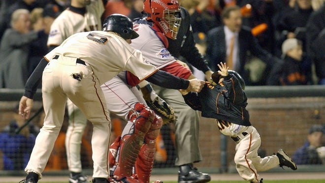 FILE - In this Oct. 24, 2002, file photo, San Francisco Giants' J.T. Snow, left, drags 3-year-old Darren Baker, son of then-Giants manager Dusty Baker, away from home plate and the path of oncoming baserunner David Bell after scoring in the seventh inning of World Series Game 5 in San Francisco.