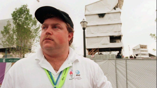 FILE- In this July 28, 1996, file photo, security guard Richard Jewell poses  across from the tower where he found a bomb and warned visitors at Centennial Olympic Park in Atlanta. When a bomb exploded in a downtown Atlanta park midway through the 1996 Olympics, it set news reporters and law enforcement on a collision course that upended the life of a security guard, turning him from hero to villain overnight. Now, more than 20 years later, a recent book and upcoming movie explore Jewell's ordeal and the roles played by law enforcement and the media.