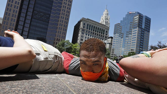 Loren Jameal Gwynn, as part of a protest outside the Statehouse on Saturday, lies on the ground for eight minutes and forty-six seconds, the amount of time that George Floyd was pinned to the ground by a Minneapolis police officer before his death.
