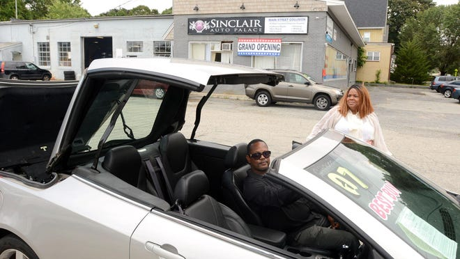 Aldrenia Davis, owner of Sinclair Auto Palace, and her husband and used car manager Michael Davis show a 2007 Pontiac G6 GT convertible hardtop for sale Thursday at newly opened Main Street used car dealership in Moosup.