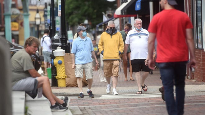 People walk in Portsmouth's Market Square with some of them wearing masks outside and some not Tuesday.