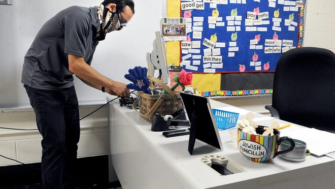 Nick Malkasian, of CommLink Integration, installs video and audio conferencing units for streaming in the second-grade class of Rebecca Martinez at St. Bridget School in Framingham.