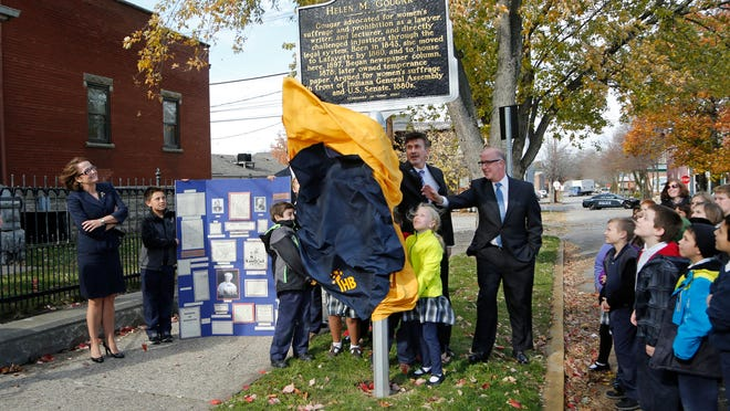 Indiana Supreme Court Chief Justice Loretta H. Rush, left, looks on Monday as a state historic marker honoring Tippecanoe County's first female lawyer, Helen Gougar, is unveiled at 914 Columbia St. in downtown Lafayette.
