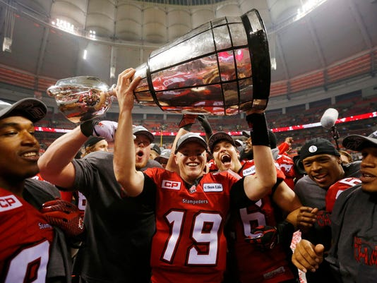 Calgary Stampeders' quarterback Bo Levi Mitchell holds the Grey Cup after the Stampeders defeated the Hamilton Tiger Cats in the CFL's 102nd Grey Cup football championship in Vancouver