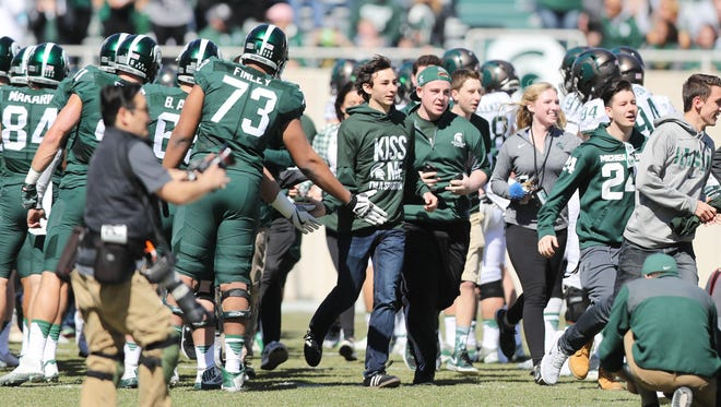 Michigan State players and fans take the field before the spring game at Spartan Stadium, Saturday, April 1, 2017.
