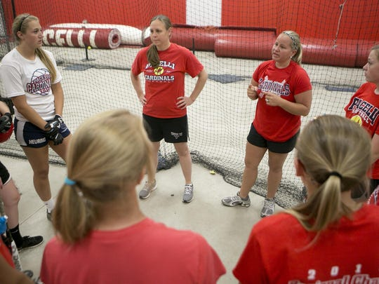 Pacelli's assistant softball coaches Beth Boden Nemec, left, and Stephanie Treichel, right, talk to the softball players during practice in the batting cages at Pacelli High School in Stevens Point, Friday, June 12, 2015.