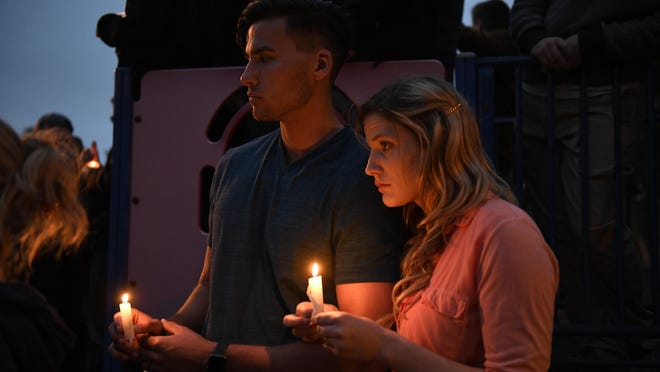 A couple joins others at a vigil held for victims of the Chabad of Poway synagogue shooting, Sunday, April 28, 2019, in Poway, Calif.