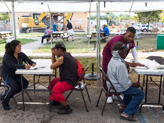 Catalina Rosales, left, helps a man fill out a survey