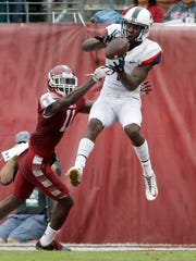 Connecticut's Tre Bell, right, catches a pass in front of Temple's Linwood Crump during a 2017 game.