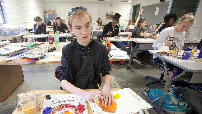 Puckett High School freshman Brady Williams uses one hand to mark the border of a color as he paints with the other during art class. Williams suffers from a rare eye disease that caused him to become legally blind.