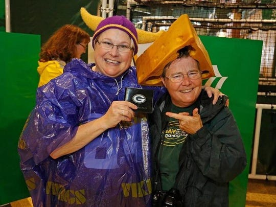 "Two fans at Lambeau Field show off the ""lost wallet"" they found Thursday during the Green Bay-Minnesota game."