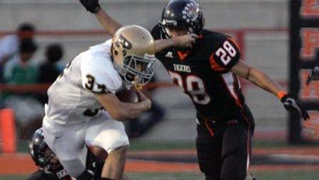Andy Banuelos of Austin High School tries to break the tackle by El Paso High defenders in 2011 at El Paso High School.