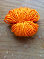 Once removed from cardboard, tie your yarn loop in the middle with a short piece of yarn.