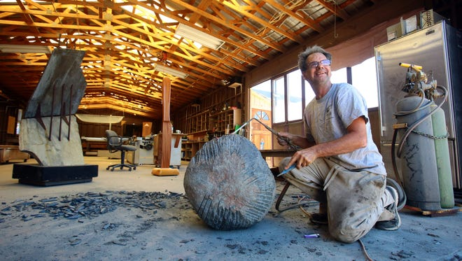 Sculptor Steve Webster talks while carving a granite boulder with a flame and chisel at his Pinyon area workshop. When finished, the boulder will be suspended as part of Webster's next sculpture.