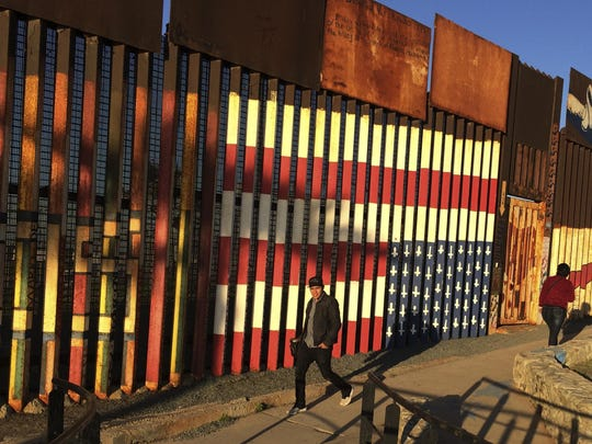 People walk past graffiti along a border structure in Tijuana.