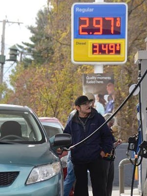 A motorist refuels at a gas station where prices have dipped below $3 per gallon Oct. 27, 2014, in Pittsfield, Mass. A national survey of gas prices reports that the average cost of U.S. regular grade gas dropped 18 cents per gallon in the last two weeks.