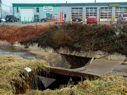 A sinkhole in the bed of Willis Run creek in West Manchester Township near Meineke Car Care, photographed on Wednesday, Jan. 15, 2014, is scheduled to be filled next week by H&H General Excavating of Spring Grove. Chris Dunn -- Daily Record/Sunday News