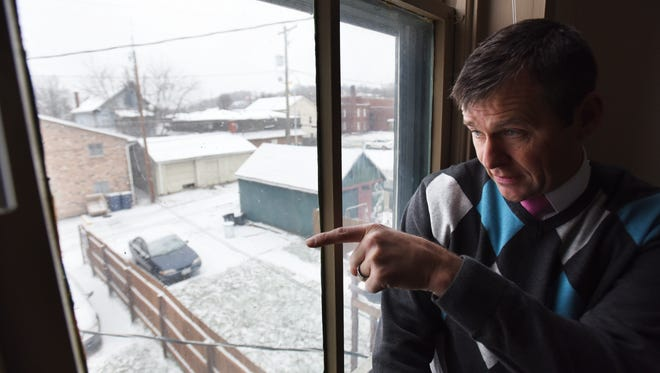 Scott Webb points out activity in the alley behind his office on Market Street in Zanesville. Webb has had to install security equipment because of illegal activity in the surrounding area.