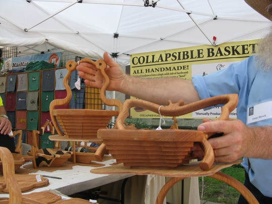 Jonas Schrock shows two of his oak folding baskets at the Park Avenue Summer Arts Fest..