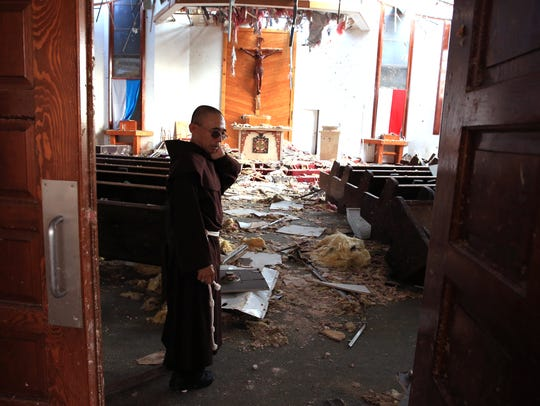 The Rev. John Tran Nguyen surveys the heavily damaged