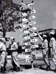 Soldiers stand near a direction sign at Camp Shanks.