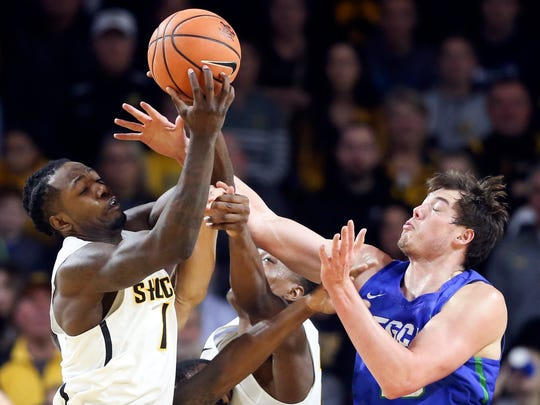 Wichita State forward Zach Brown, left, fights for a rebound with Florida Gulf Coast forward Ricky Doyle during the first half of an NCAA college basketball game Friday, Dec. 22, 2017, in Wichita, Kan. (Travis Heying/The Wichita Eagle via AP)