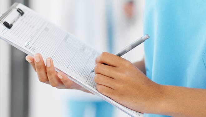 Stock photo: Close-up of a young surgeon holding clipboard with colleague in background