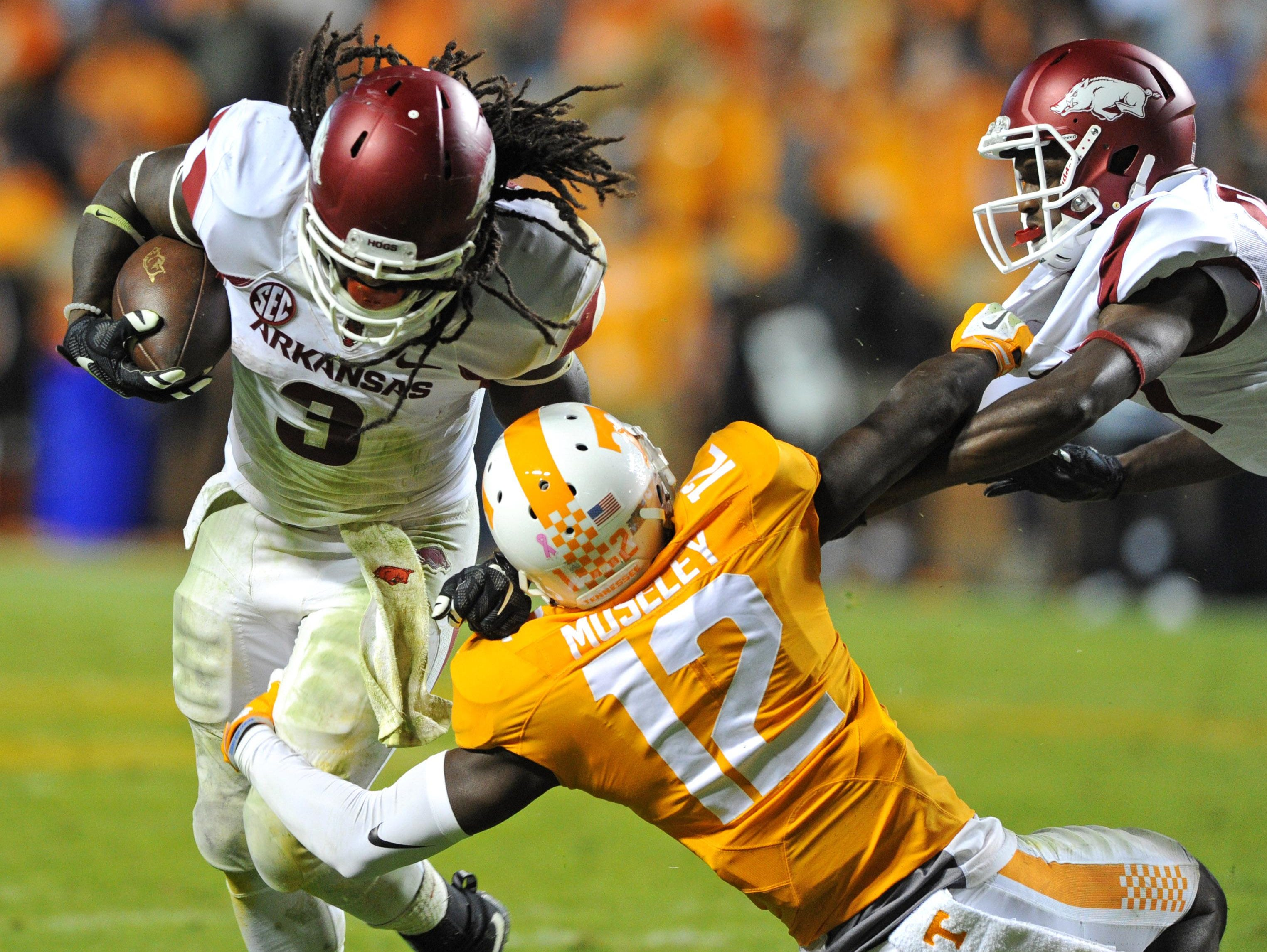 Arkansas running back Alex Collins (3) gets by Tennessee defensive back Emmanuel Moseley (12) with help from Arkansas wide receiver Dominique Reed during the second half at Neyland Stadium in Knoxville, Tenn. on Saturday.