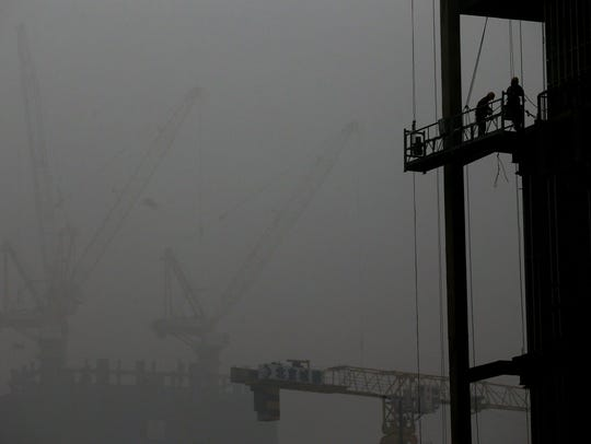 Chinese workers are silhouetted against the smog  in