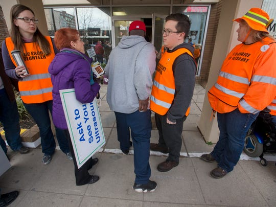 Donna Durning, in purple, talks to a man who is entering the EMW Women's Surgical Center, while volunteer escorts at the center make sure that no protesters cross the white line. Feb. 11, 2017.