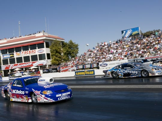 Kurt Johnson (front) and Allen Johnson race while the crowd enjoys the second day of qualifying for NHRA & POWERade racing at Firebird Raceway Chandler.