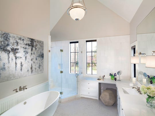 A trendy light fixture will illuminate other design elements you select, like the modern tub, glass shower and abstract art in this bathroom.
