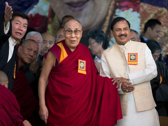 Tibetan spiritual leader the Dalai Lama holds hand with junior Indian Minister for Culture and Tourism Mahesh Sharma, with prime minister of the self-declared Tibetan government-in-exile Lobsang Sangay, left, standing by his side at an event marking the beginning of the 60th year of the spiritual leader's exile in India, in Dharmsala, India, Saturday, March 31, 2018. Sangay on Saturday urged his compatriots to strengthen efforts to make the return of the Dalai Lama to his native land a reality.