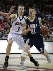 Xavier's Hunter Plamann dribbles past Marcus Domask of Waupun during the WIAA Division 3 state championship game March 19 in Madison.