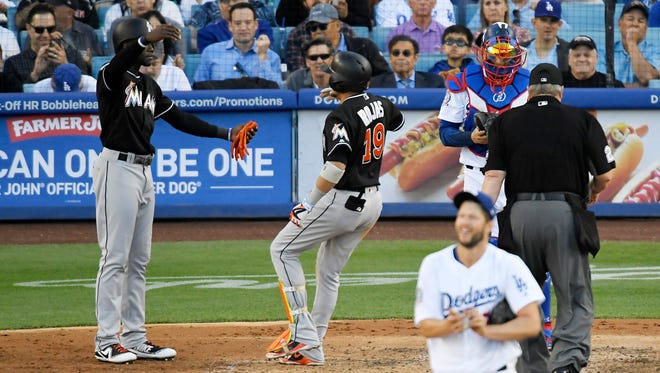The Marlins' Miguel Rojas, center, is congratulated by teammate Cameron Maybin after hitting a three-run home run Wednesday off Dodgers pitcher Clayton Kershaw.