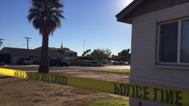 Crime scene tape surrounds an area where Phoenix police shot and injured someone near Freeway Baptist Church on Nov. 23, 2015.